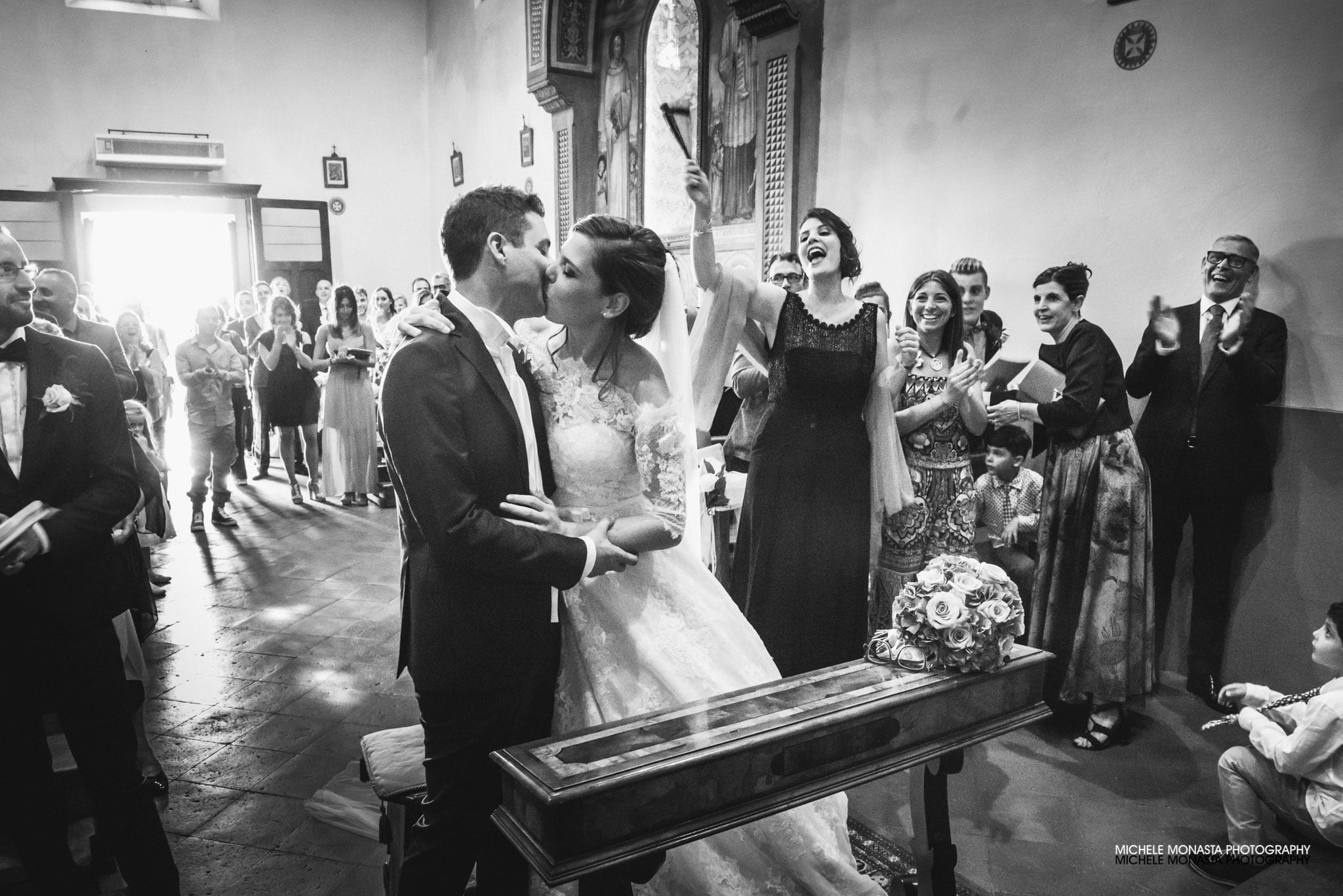 The groom and the bride kiss as soon as they got married in the church italian wedding in tuscany