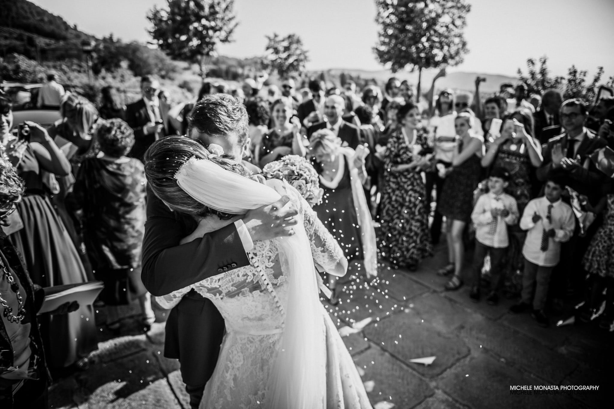The groom and the bride kiss as soon as they leave the church after a italian wedding in tuscany
