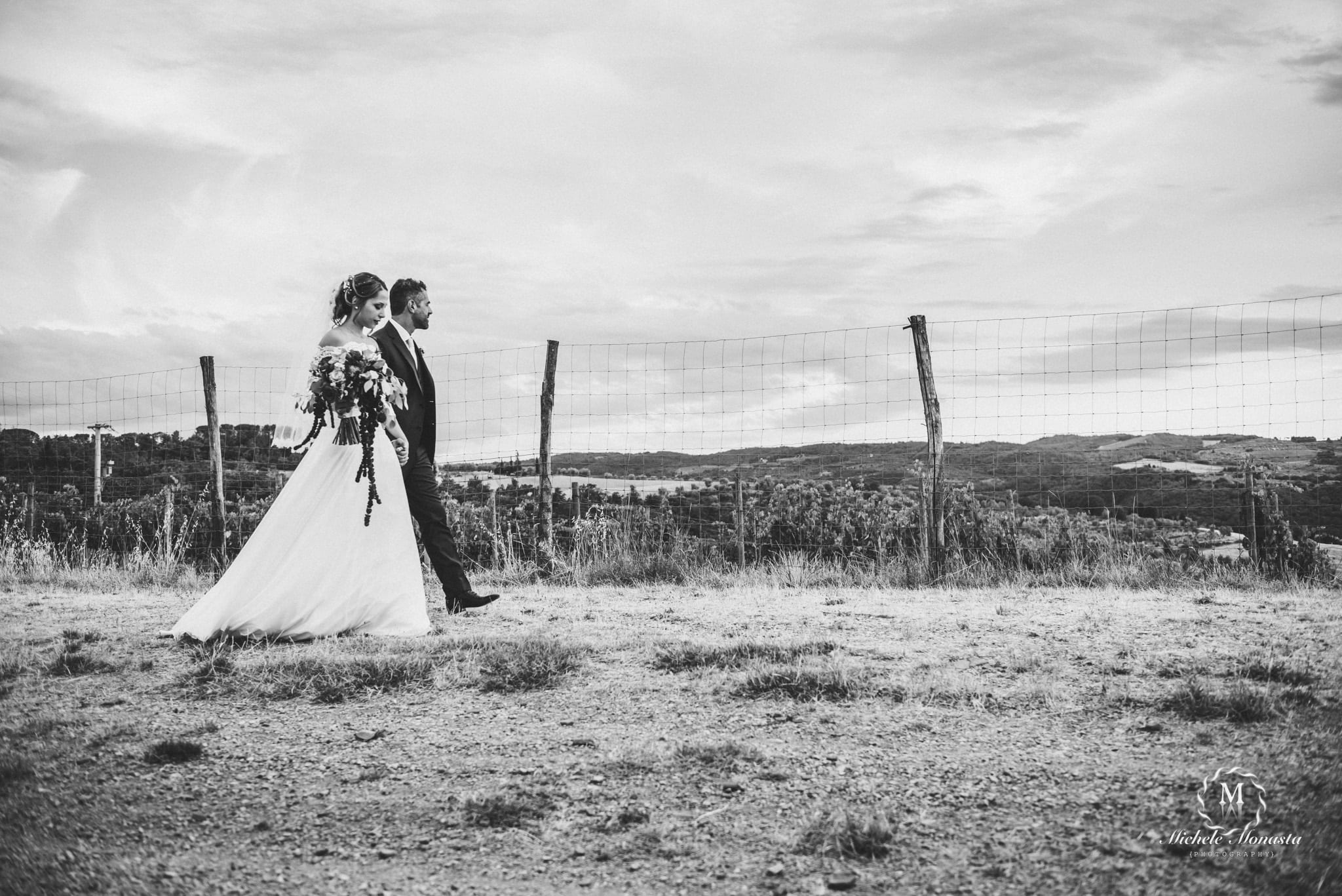 bride and groom walk together on their wedding day in tuscany