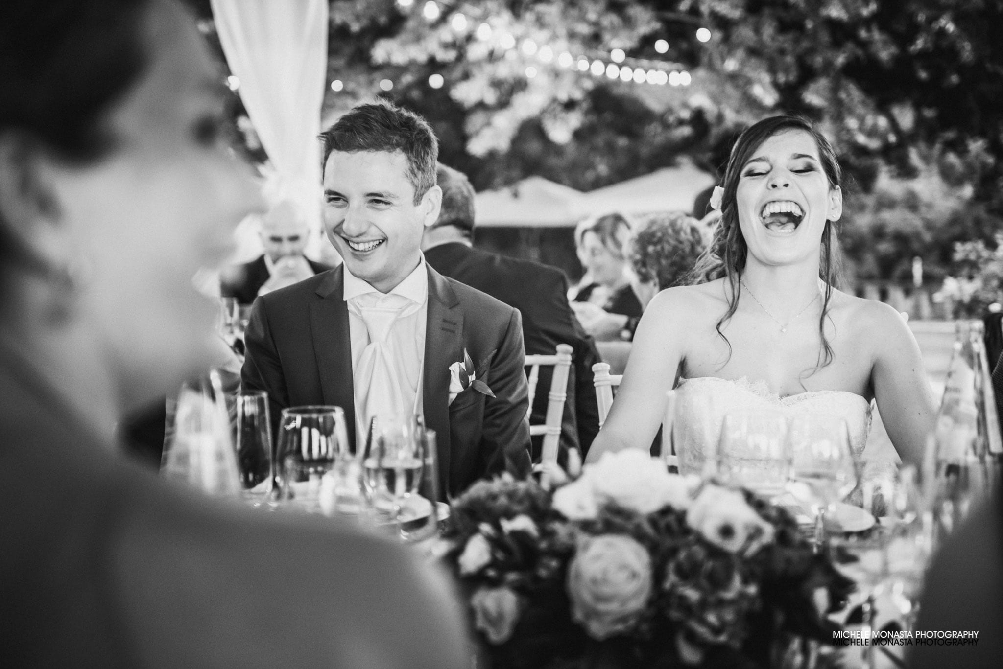 The bride and the groom laugh during their wedding dinner in Tuscany